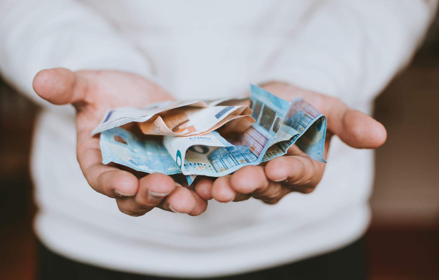 Man with his hands out holding a fist-full of money