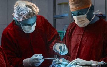 the healthcare debate, NHS, two surgeons are operating on a patient